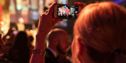 A woman taking a photo of a stage at an awards ceremony at Grosvenor House Hotel in London