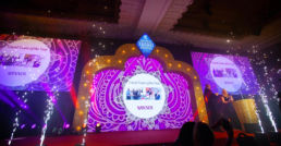 Sparks going off on stage at an awards ceremony in front of a golden arch Bollywood theme.
