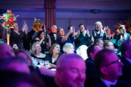 An audience applauding and taking pictures at an awards ceremony at Grosvenor House Hotel in London
