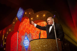 Dara O Briain on stage at an awards ceremony with a golden arch at Grosvenor House Hotel in London
