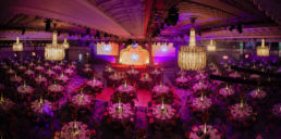 Tables and award ceremony set up at Grosvenor House Hotel in London with a large stage and golden arch.