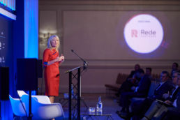 A speaker on stage at a conference event with digital branding on the walls at the Landmark Hotel London