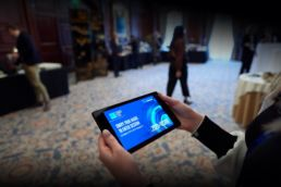 A woman using a tablet to register for a conference at the Landmark Hotel, London