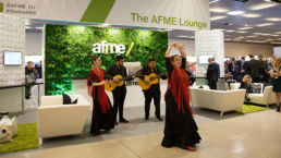 An exhibition stand with a living plant wall at an event with performers