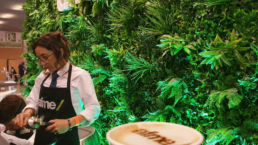 An exhibition stand with a living plant wall at an event and coffee machine
