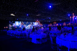 A stage set and tables at an awards ceremony at Battersea Evolution in London.
