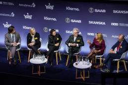 A panel of men and women sitting on stage at a conference at Ham Yard Hotel in London.