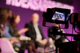 A camera filming a panel of men and women on a large stage at a conference at World Travel Market, ExCel London.