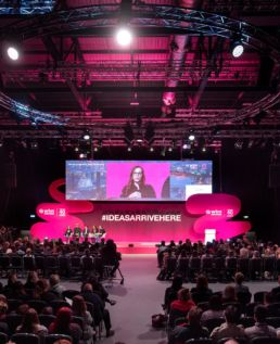 A panel of men and women on a large stage at a conference at World Travel Market, ExCel London.