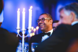 A man laughing at an awards ceremony and gala dinner.
