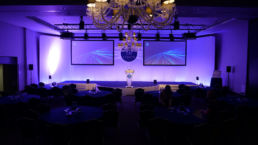 A conference stage with purple lights, two screens and a lectern.