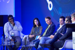 A panel of speakers onstage at a conference event at the Landmark Hotel London
