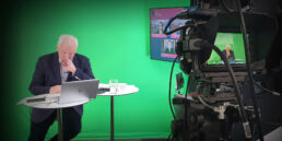 Nik Gowing hosts a hybrid event live in a studio with a remote panel.