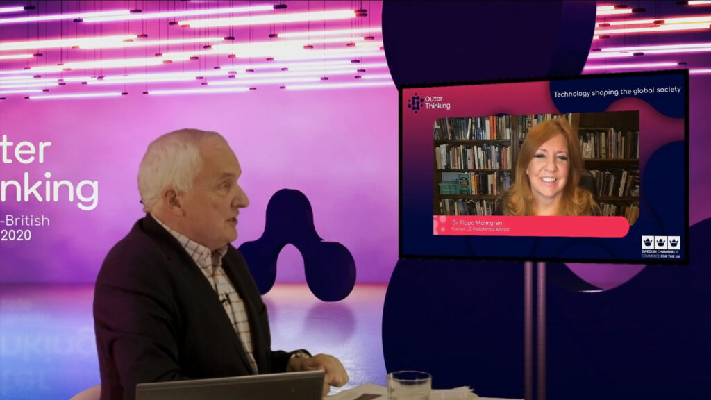 Nik Gowing hosts a hybrid virtual conference from within a green screen studio and speaks with a remote presenter on a screen.